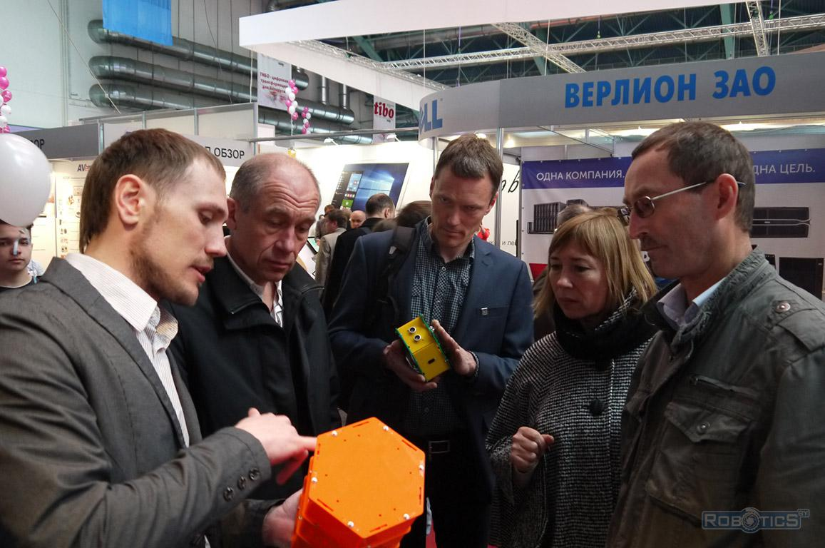 Grigory Prokopovich and Mikhail Kovalev tells about the benefits and features constructor RoboCake Beginner near the stand of the exhibition colleagues from the University of Norway
